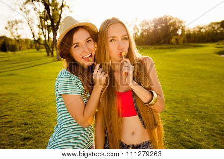 Two Playful Sexy Girls Licking Lollipops