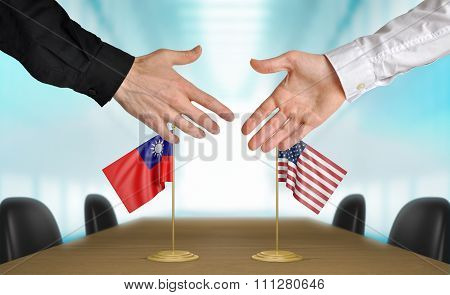 Taiwan and United States diplomats shaking hands to agree deal