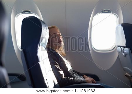 Lady traveling napping on a plain.