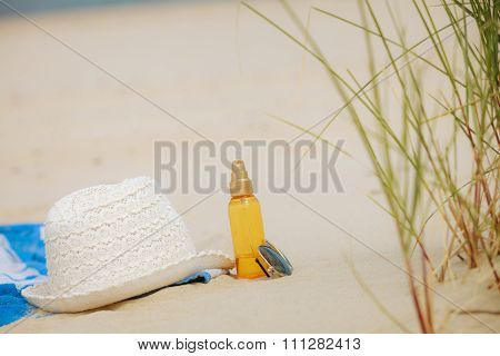 Beach Set Hat And Sunscreen Lotion Lying On Sand