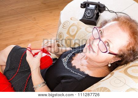 Elderly Grandmother Sitting Knitting In A Chair