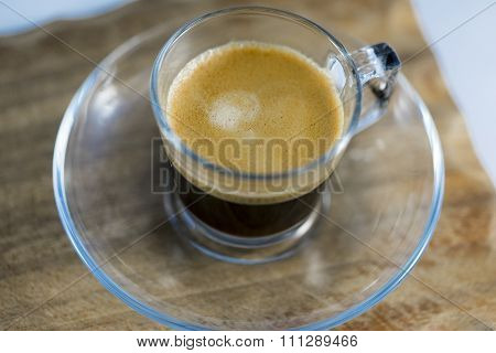 Frothy Black Coffee In Glass Mug On Table
