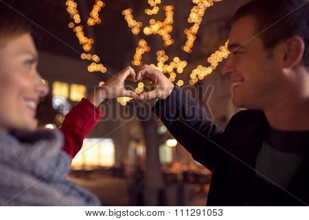Affectionate couple looking at each other and making heart shape with hands on Christmastime