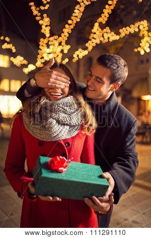 romantic man covering his girlfriend 's eyes, man standing behind woman with gift on street with Christmas decorated