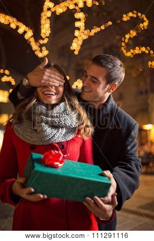 Man surprising a woman with a gift on Christmastime