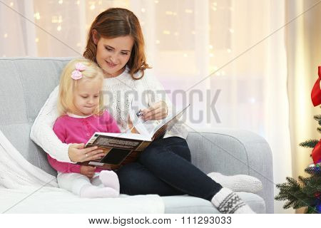 Mum reading book to daughter in Christmas living room
