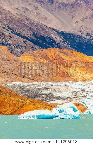 The picturesque multi-colored shore of Lake Viedma. Massive glacier descends into the emerald water. In the water ice-floes, broken away from a glacier