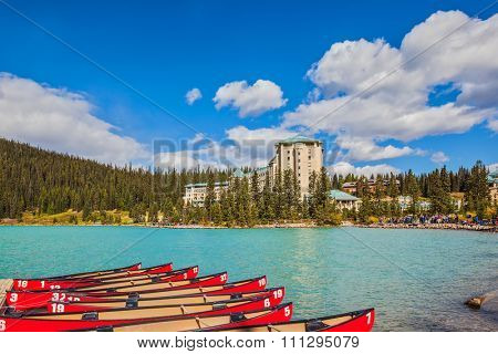 Lake Louise on a beautiful sunny day. At the pier moored red canoe for tourists