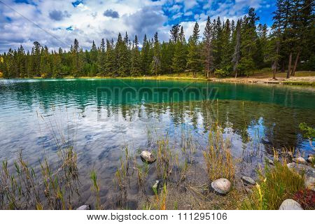 The picturesque oval lake with clear water. Canadian Rocky Mountains, lake Annette, Jasper National Park
