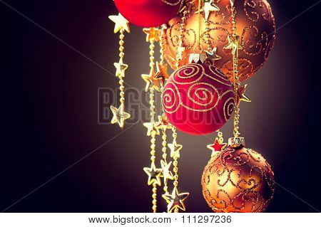 Christmas and New Year decorations border Design. Hanging Christmas Baubles and Garland over dark background