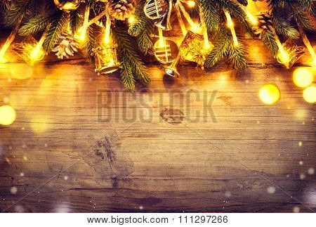 Christmas fir tree with decoration on dark wooden board background. Border art design with Christmas tree, baubles and light garland