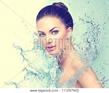 Beautiful Model Spa Woman with splashes of water. Beautiful Smiling girl under splash of water with fresh skin over blue background. Skin care, Cleansing and moisturizing concept. Beauty face