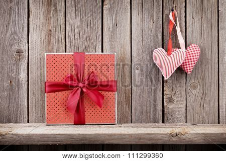Two Valentines day hearts and gift box in front of rustic wooden wall