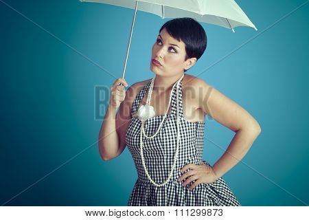 Bored girl vintage 50s dress with white umbrella over blue background