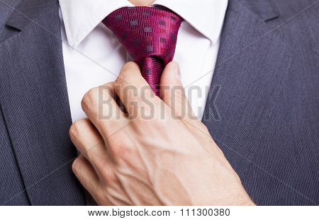 Man in a suit fixing his tie