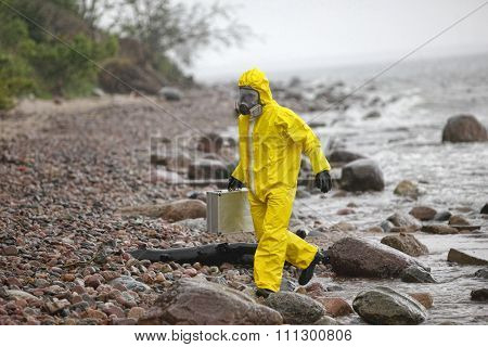 scientist in protective suit with silver case walking in water at rocky beach - back view
