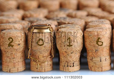 Closeup of a large group of Champagne corks, that fill the frame with the date 2016. Selective focus on the front row. One cork has the metal cage. Horizontal format.