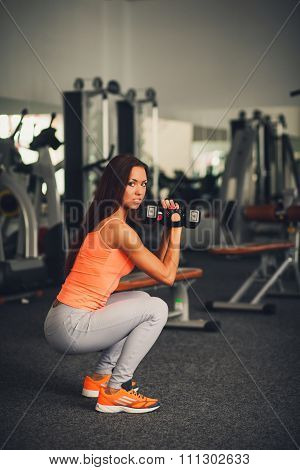 Sports Young Girl Squats With Dumbbells In The Gym