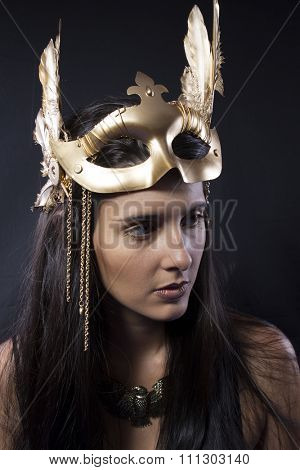 Brilliance sensual young woman with golden mask jewelry