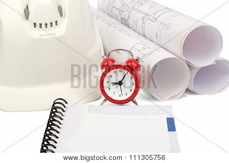 Blueprint rols and helmet with alarm clock