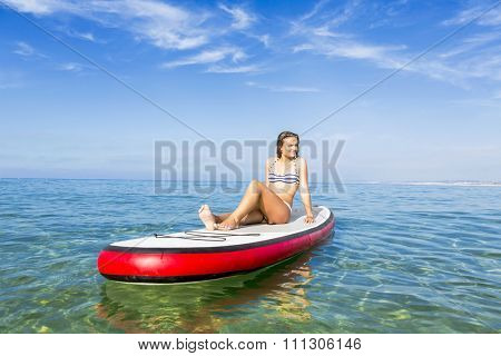 A beautiful woman sitting over a paddle surfboard and relaxing on a beautiful sunny day