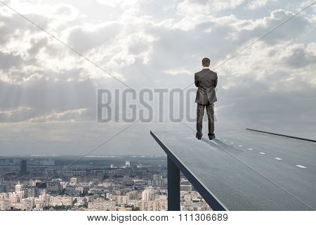 Businessman standing on road in sky