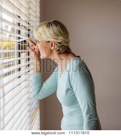 happy senior woman peeking through the blinds