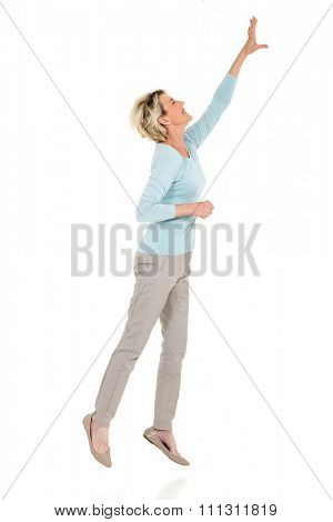 active senior woman jumping up and reaching out on white background