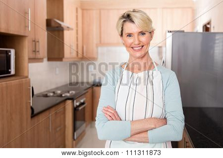 smiling mid age woman in kitchen with apron