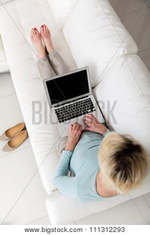 overhead view of mid age woman working on laptop computer at home
