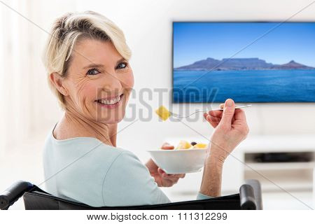 happy handicapped elderly woman eating fruit salad at home