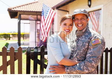 american military couple hugging outside home