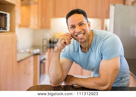 handsome mid age man leaning against the kitchen counter