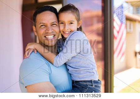happy middle aged american man holding his daughter outside their house