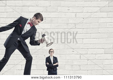 Aggressive businessman screaming in megaphone on her colleague