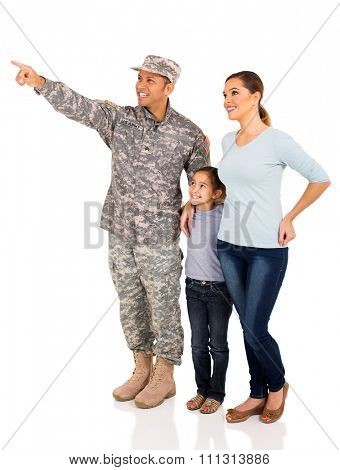 beautiful military family pointing at empty copy space on white background