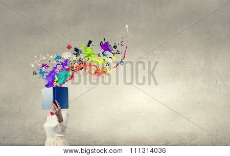Woman with opened book against her face and colorful splashes flying out