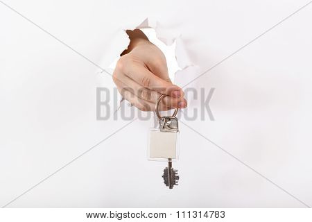 Hand Holds The Keyring Through A Hole