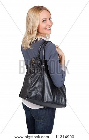 Young blond woman with bag looking over her shoulder