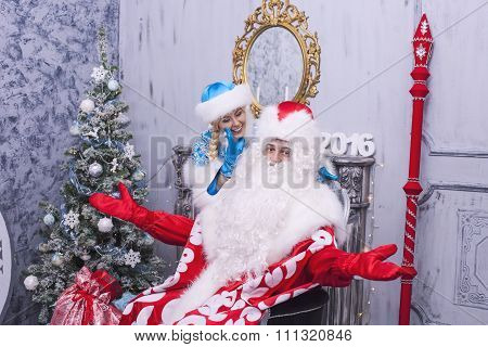 Santa Claus And Snow Maiden Smiling In The Beautiful Interior With Christmas Tree