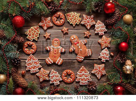 Gingerbread man and woman couple, fir tree, stars, christmas cookies composition with xmas tree deco
