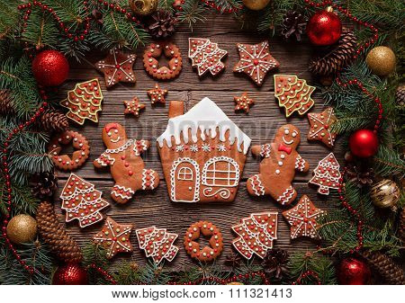 Gingerbread man and woman couple, house, fir trees, stars cookies composition in christmas decoratio