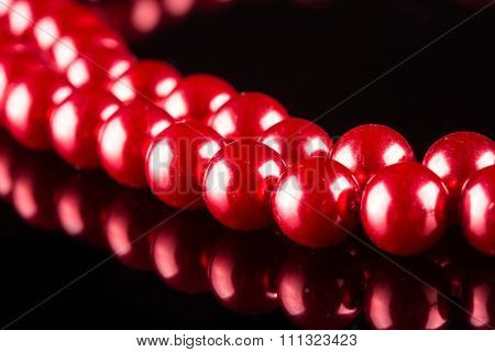 necklace of red pearls on black background