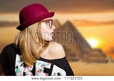 Charming girl in hipster glasses on Egypt pyramid blurred background
