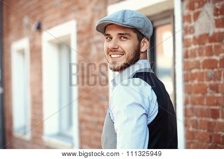 casual young man stands with his back against brick wall