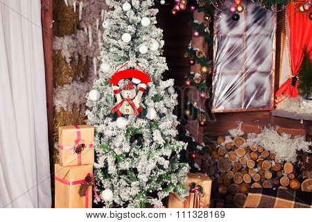 New Year and Christmas Tree near wooden house and window. Green, red, brown and white colors. Snow,