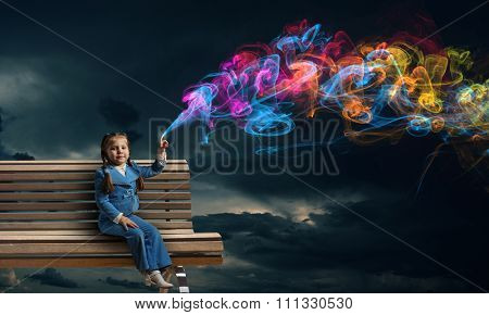 Little girl sitting on wooden bench and pointing with finger up