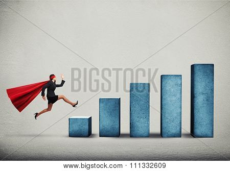 purposeful businesswoman in superhero cloak running up on diagram over grey background