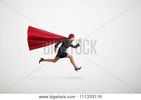 serious businesswoman wearing like superhero very fast running over light grey background