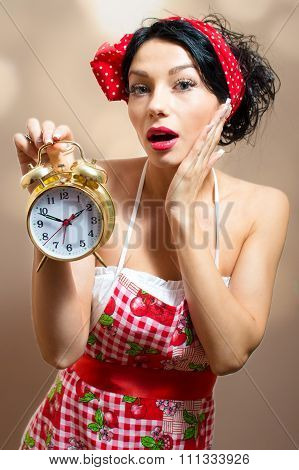 Young pinup lady in Alice band, apron holding alarm clock